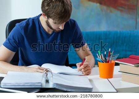 Attractive student making notes in his notebook - stock photo