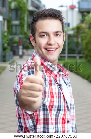 Attractive student with checked shirt showing thumb up - stock photo