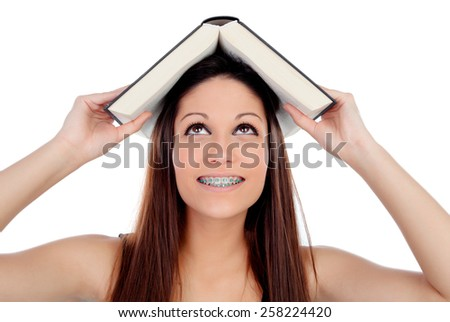 Attractive student woman with brackets an a book on the head isolated on a white background - stock photo
