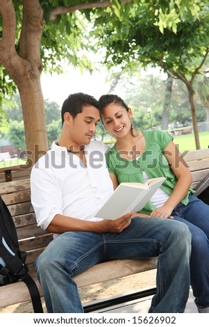 Attractive students at college sitting on bench