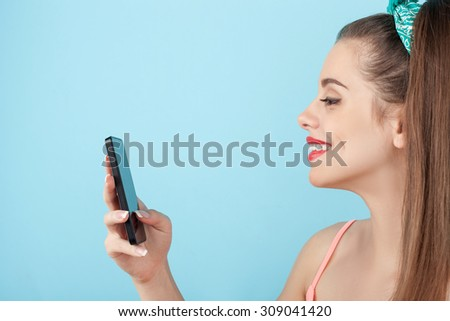 Attractive styled girl is standing and smiling. She is holding a mobile phone and messaging to someone. The lady is smiling happily. Isolated on blue background - stock photo