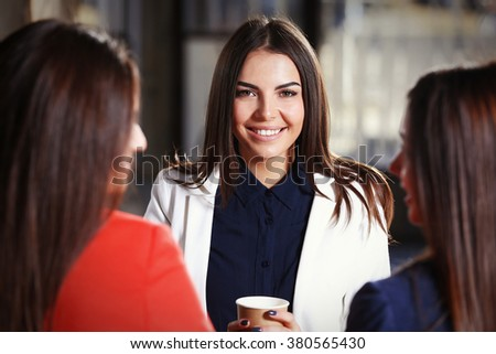 Attractive stylish girls  with cup of coffee speaking in cafe