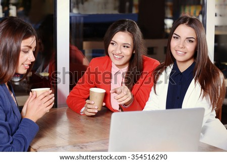 Attractive stylish girls with with laptop speaking in cafe
