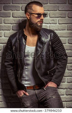 Attractive stylish man with beard in leather jacket and sunglasses looking away, standing against brick wall