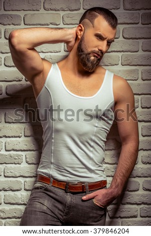 Attractive stylish man with beard looking down, hand behind the head, standing against brick wall - stock photo