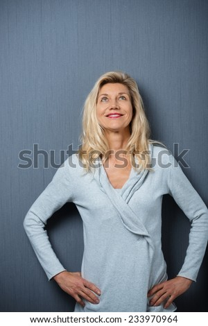 Attractive stylish middle-aged blond woman standing thinking with her hands on her hips staring up into the air with a dreamy expression and smile of pleasure, dark studio background - stock photo