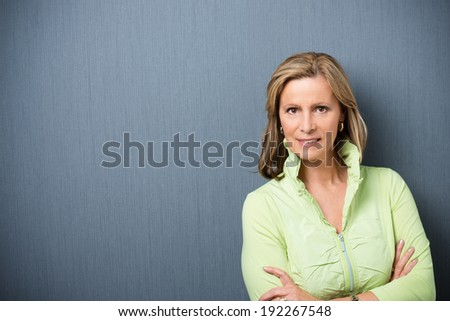 Attractive stylish middle-aged woman with shoulder length blond hair standing with folded arms looking at the camera with a smile, on grey with copyspace - stock photo