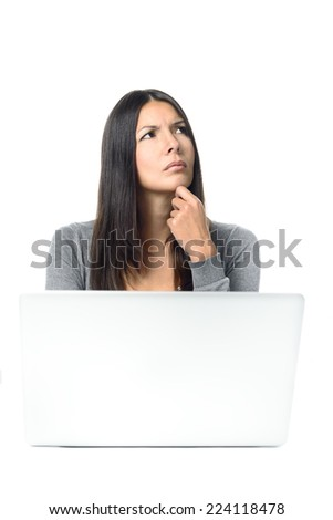 Attractive stylish young businesswoman with a worried frown sitting thinking behind her laptop at her desk staring up into the air with her hand to her chin and a serious expression - stock photo