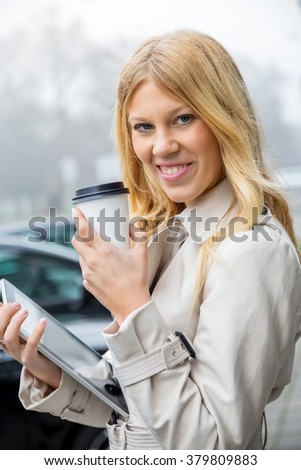 Attractive stylish young woman waiting in an urban street standing on the sidewalk holding a cup of takeaway coffee and tablet looking expectantly down the road with a serious pensive expression