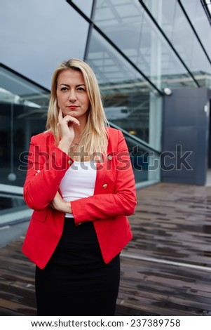 Attractive successful business woman looking confident standing against skyscraper office building, blond hair executive business woman dressed in red jacket standing near skyscraper building - stock photo