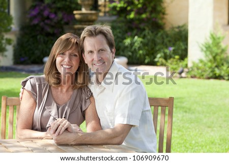 Attractive, successful, happy middle aged man and woman married couple in their thirties, sitting together outside in a garden sitting at a table. - stock photo