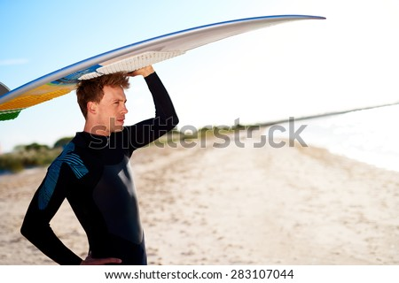 Attractive surfer balancing his surfboard on his head as he stands on a sandy tropical beach looking out over the ocean and surf, close up profile view - stock photo