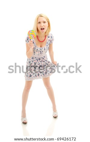 Attractive surprised  blonde with lollipop holding her dress, looking like a littile girl