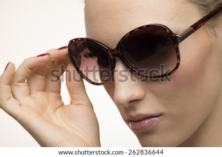 Attractive surprised young woman wearing sunglasses on brown back - stock photo