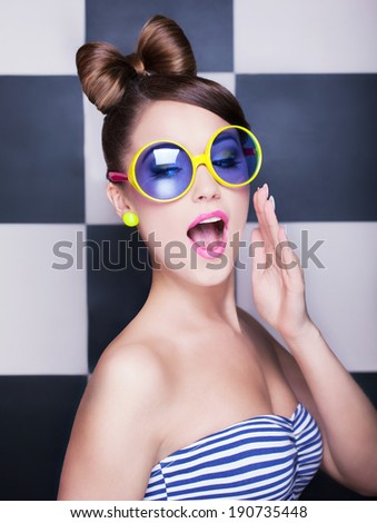 Attractive surprised young woman wearing sunglasses on checkered background, beauty and fashion concept  - stock photo