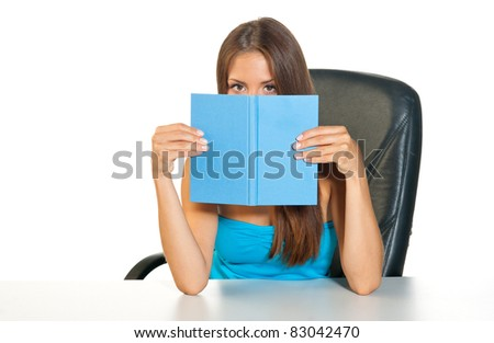 attractive teen girl hiding behind open book - stock photo