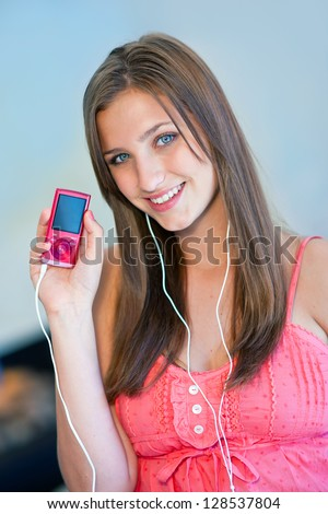 attractive teen girl holding pink mp3 player and listen music