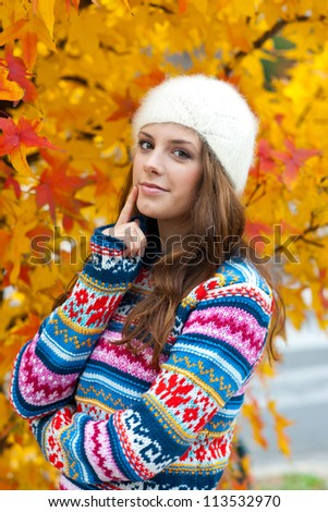 attractive teen girl in front of the colorful autumn leaves