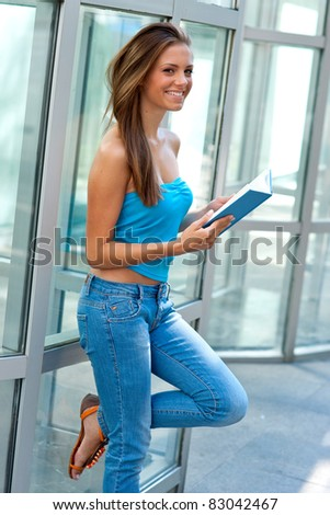 attractive teen girl reading book and learning outside
