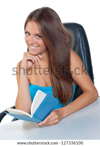 attractive teen girl sitting at the table and reading book - stock photo