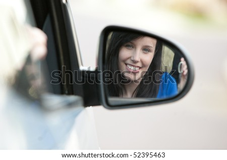 Attractive teen girl sitting in her car holding keys after bying a new car - stock photo