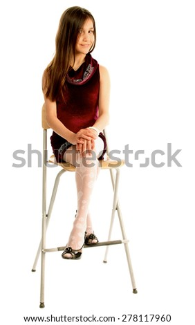 Attractive Teen Girl with Long Brown Hair in Purple Dress Sitting on Chair and Posing isolated on white background - stock photo