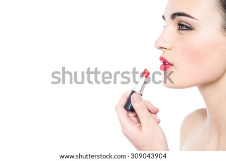 Attractive teen model applying red lipstick over white - stock photo