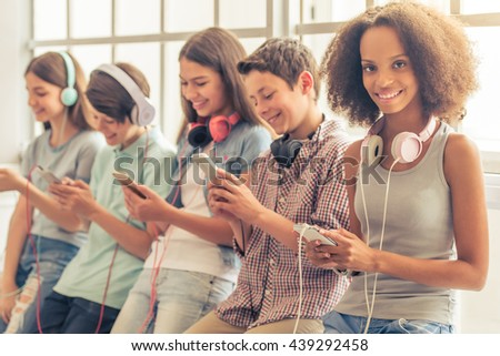 Attractive teenage Afro American girl with headphones is using a smartphone, looking at camera and smiling while sitting among other teenagers - stock photo