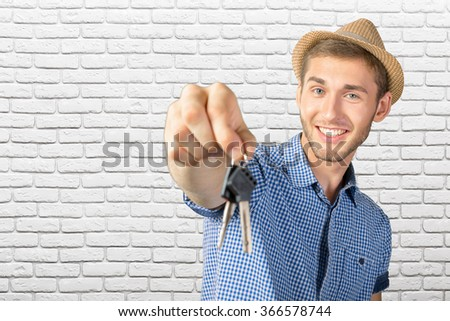 Attractive teenage boy holding car keys - stock photo