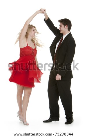 Attractive teenage couple dancing on isolated white background - stock photo