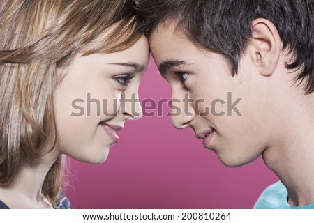 Attractive teenage girl and boy looking at each other smiling - stock photo