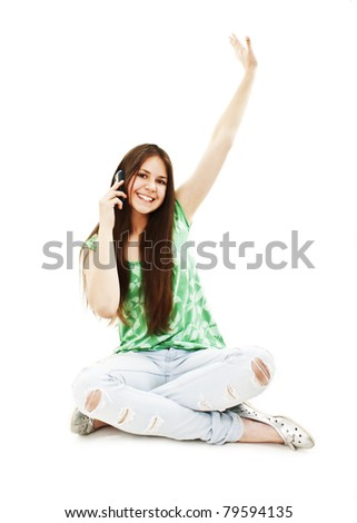 Attractive teenage girl cheering during phone call. All on white background.