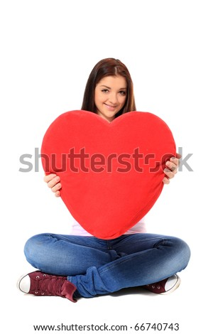 Attractive teenage girl holding heart-shaped red pillow. All on white background. - stock photo