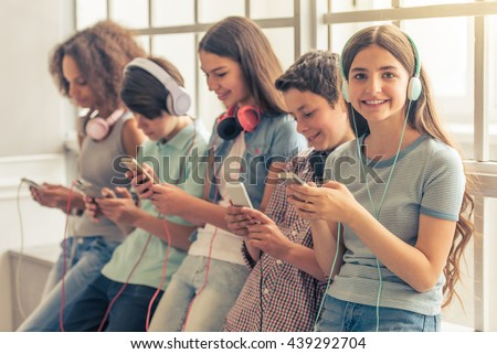 Attractive teenage girl in headphones is listening to music using a smartphone, looking at camera and smiling while sitting near other teenagers - stock photo