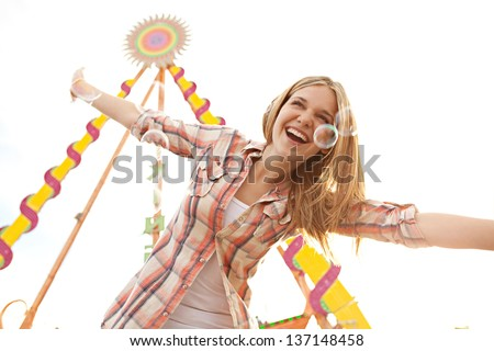 Attractive teenage girl playing with bubbles in an amusement park arcade with rides and the sky behind her. - stock photo