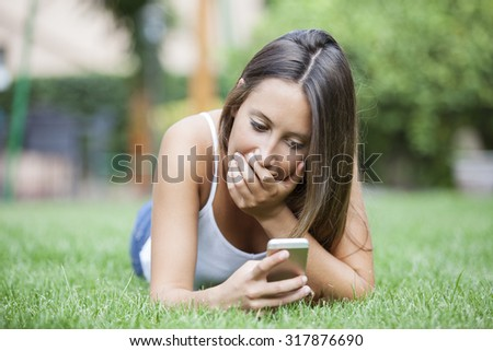 Attractive teenage girl receiving a surprising text while sitting in a park