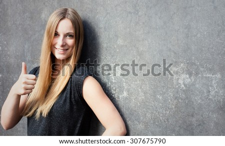 Attractive teenage girl showing thumbs up - stock photo