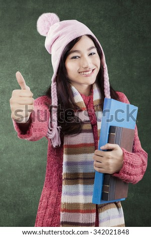 Attractive teenage girl wearing winter clothes, showing thumbs-up while holding book in the class - stock photo