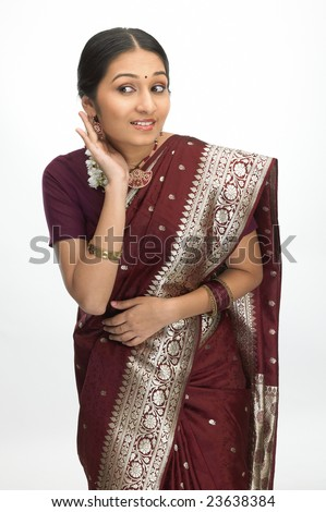 Attractive teenage girl with sari trying to hear - stock photo