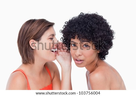 Attractive teenager being told a secret by a friend - stock photo