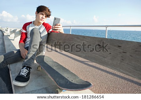 Attractive teenager boy relaxing with a skateboard and sitting down on a bench by the sea, holding a smartphone mobile technology during a sunny day, outdoors. Teens lifestyle. - stock photo