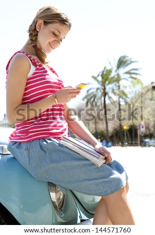 Attractive teenager girl using her smartphone cell phone while sitting on a classic car in a city with a sunny sky, looking at the camera and smiling. - stock photo