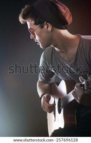 Attractive teenager rock star on stage playing acoustic guitar - stock photo