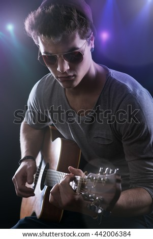 Attractive teenager rock star on stage playing acoustic guitar