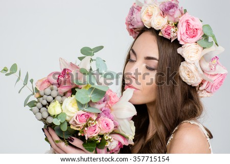 Attractive tender young woman in roses wreath holding and smelling beautiful bouquet of flowers over white background - stock photo