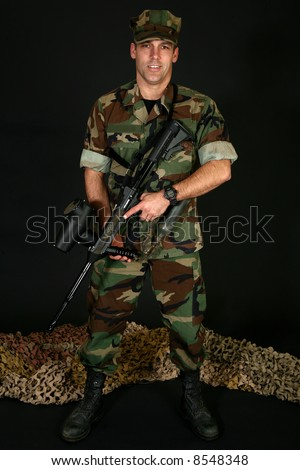 Attractive thirty something man in camo fatigues with paintball rifle over black. - stock photo