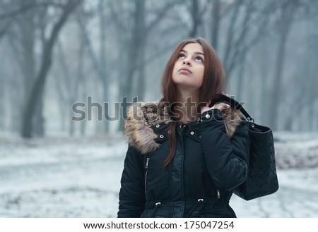 Attractive thoughtful teen girl in wintertime outdoor - stock photo
