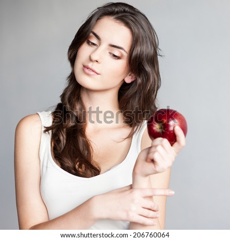 attractive thoughtful young casual caucasian brunette  woman in white singlet holding red apple over gray background - stock photo