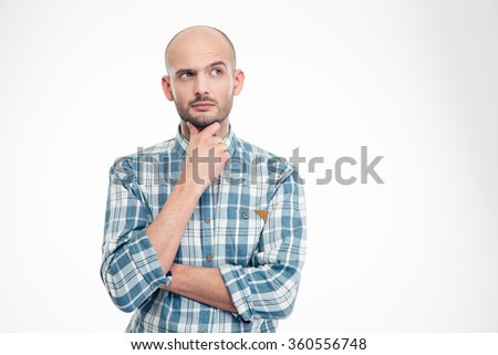 Attractive thoughtful young man in plaid shirt looking away over white background - stock photo