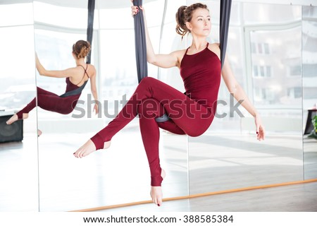 Attractive thoughtful young woman doing pose of aerial yoga using hammock - stock photo